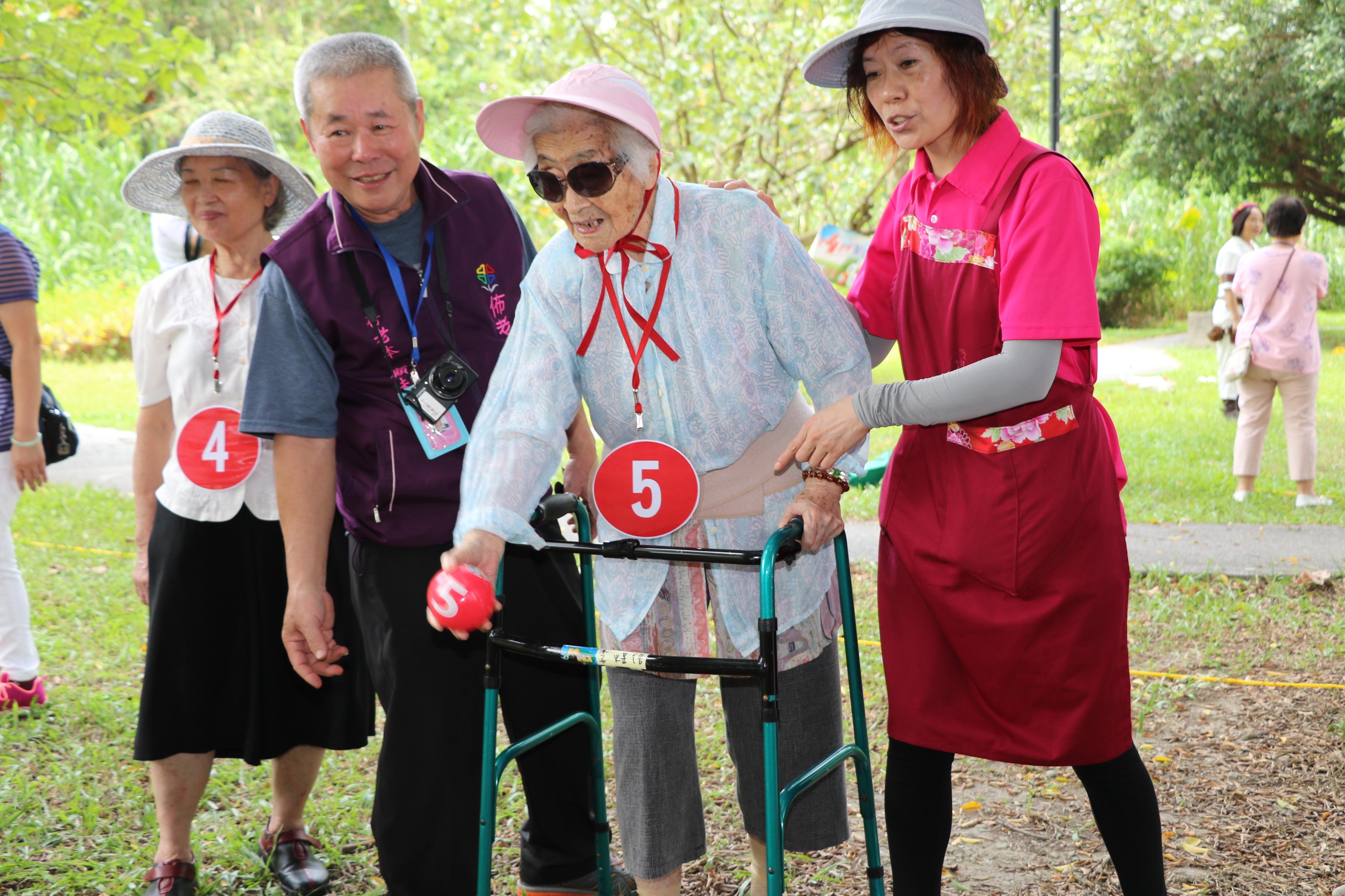 高齡92歲的李煜信奶奶在照服員和佈老志工的協助下玩高智爾球